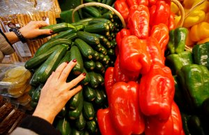 A greengrocer arranges zucchinis and sweet peppers on a vegetables stall in Marseille